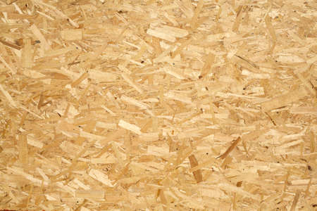 sandy brown: Wooden panel made of pressed of sandy brown wood shavings as background closeup