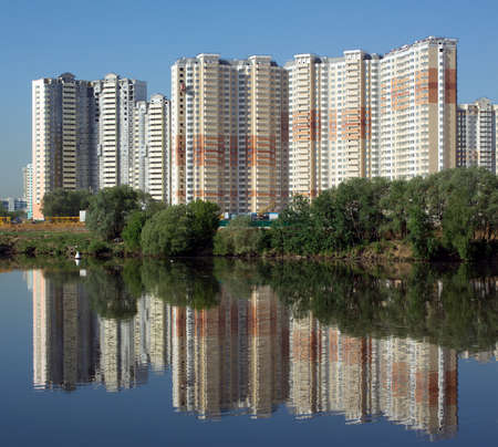 constructed: Constructed block of flats over river and clear blue sky in summer day