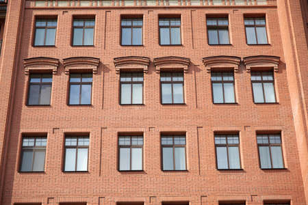 storied: Front view of brick wall red contemporary apartment building with windows closeup Stock Photo