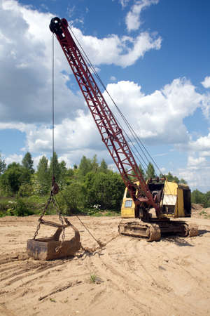 crane bucket: Yellow excavator with big heavy bucket standing on sand on background of forest and blue sky with white clouds on summer day vertical view