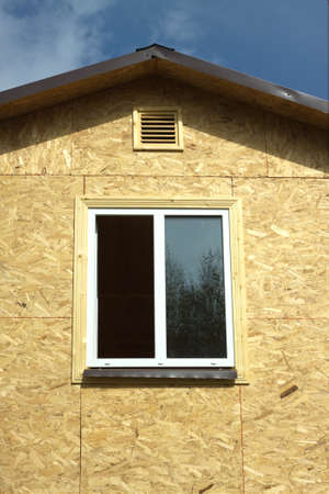 sandy brown: Wall from wooden panels made of pressed sandy brown wood shavings with white plastic window and roof in a new house vertical photo closeup