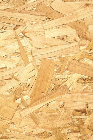 sandy brown: Wooden panel made of pressed of sandy brown wood shavings as background vertical view closeup Stock Photo
