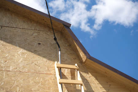 Power supply mounting on new built suburban house in summer day  Horizontal photo photo