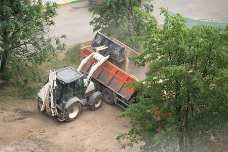 Road construction machine ship rocks and sand in an orange  lorry photo