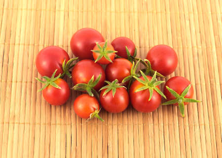 sandy brown: Heap of ripe tomatoes on sandy brown straw mat closeup Stock Photo