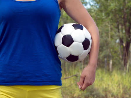 Teenage girl in blue shirt and yellow shorts holding classic ball for playing soccer. Closeup Photo photo