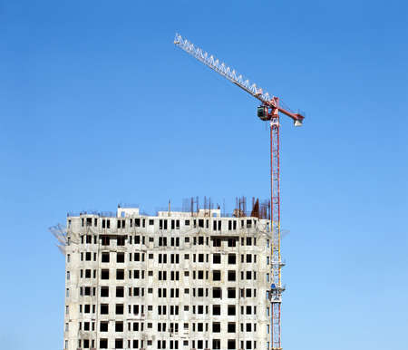 crane parts: Big hoisting tower crane and top section of modern construction building over cloudless sky. Vertical photo Editorial