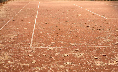 summer sport: End of summer sport season. Empty tennis court with lot of yellow leaves in autumn