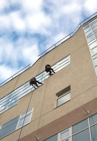 alpinist: Two industrial climbers with cleaning equipment, washes windows in a hign office building Stock Photo