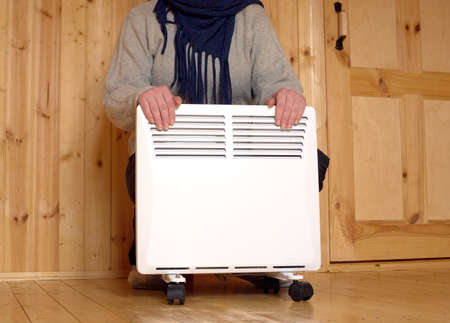 warms: Woman froze and warms her hands on white electric convector heater with horizontal louvers in room of a new wooden house