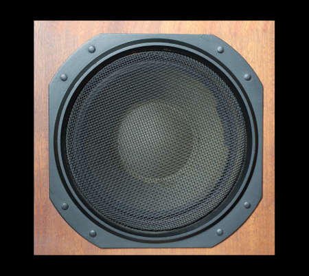 sub woofer: Subwoofer Loud speaker system with round black grill and wooden finish isolated on black closeup Stock Photo