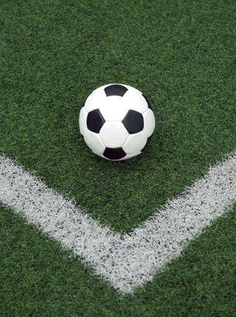 prato sintetico: Palla bianca e nera per giocare a calcio in linea nell'angolo in erba sintetica primo piano Archivio Fotografico