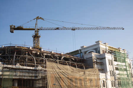 Big tower crane on the reconstruction of a residential building on blue cloudless sky background