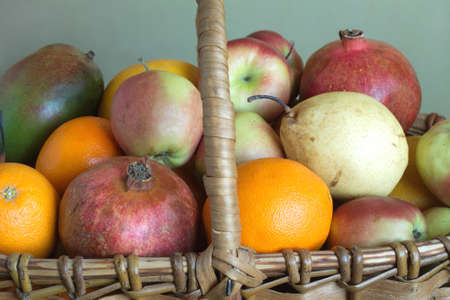 Brown wicker basket with a lot of assorted fruits closeup photo