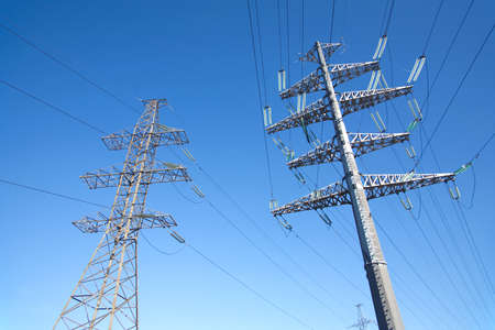 prop: High-voltage power line grey metal prop with many wires vertical view over clear cloudless blue sky bottom-up view