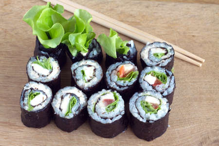 portions: Portions of sushi rolls with salad and ingredients on wooden cutting kitchen desk. Closeup photo