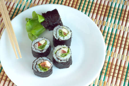 portions: Portions of sushi rolls with ingredients lies on white plate on wicker kitchen tablecloths. Photo closeup Stock Photo