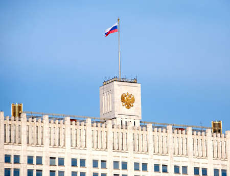 White house. Top of Russian house of parliament in Moscow with flag and coat of arms close up photo