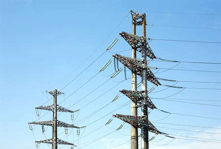 is cloudless: Two high-voltage power line grey metal props with many wires vertical view over clear cloudless blue sky bottom-up view