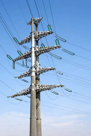 prop: Tall High-voltage power line grey metal prop with many wires vertical view over clear cloudless blue sky bottom-up view
