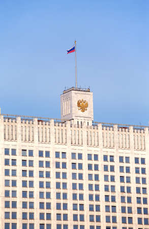 blue grey coat: Top of White house. Russian house of parliament in Moscow with flag and coat of arms close up Editorial
