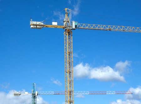 construction frame: Tower cranes in construction process over blue sky with clouds horizontal view Stock Photo