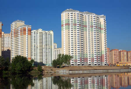 constructed: Landscape with constructed buildings in new city district after river over clear blue cloudless sky in summer day