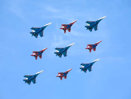 supersonic transport: Aerobatic groups Russian Knights and Swifts on MIG29 and SU27 fighters in flight against blue sky Editorial