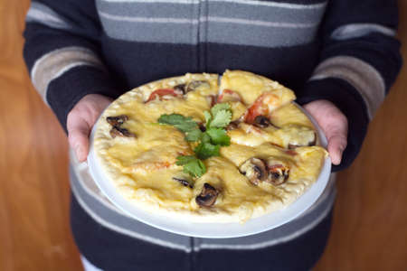 Woman in strips cloths holds large white plate delicious pizza with mushrooms tomatoes and parsley. Photo closeup photo