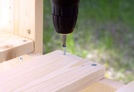 tightening: Making of wooden pallets. Tightening the screws with electric screwdriver. Photo closeup