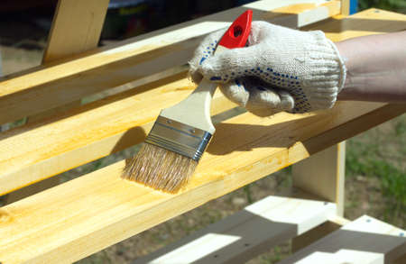 shelving: Female hand in textile glove paint wooden shelving outdoors closeup Stock Photo