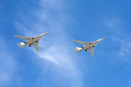 supersonic: White Swans. Russian military aircraft supersonic bombers with variable sweep wing Tu-160 in flight against blue sky