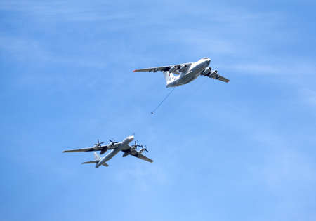 turboprop: Russian military transport plane Il-78 refueling tankers and Tu-95 turboprop strategic bomber-missile Bear in flight against the blue sky