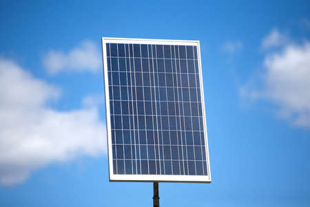 single object: Single big vertical solar panel over blue sky with blur clouds