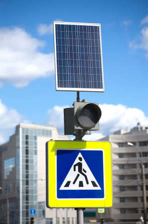 semaforo pedoni: Pedestrian crossing sign, traffic lights and solar panel for electricity alternative on city street closeup