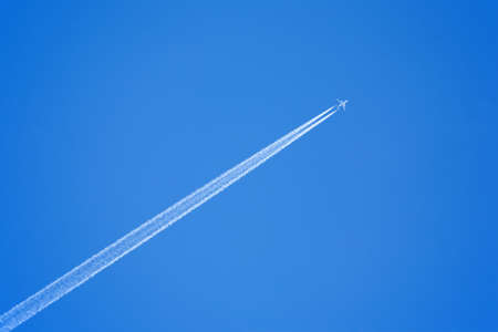 supersonic: Large passenger supersonic plane flying high in clear blue sky, leaving long white trail