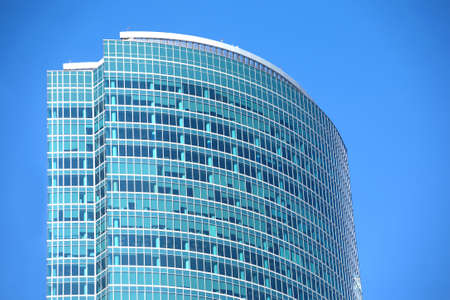 panoramic windows: Top section of modern office building from glass and metal with many large panoramic windows in business cluster vertical front view closeup