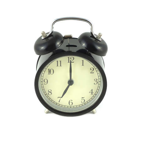 seven o'clock: Alarm clock in black case shows 7 oclock. Front view isolated on white closeup