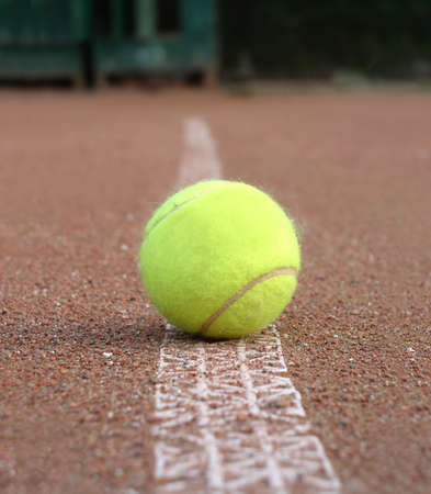 marking: Front view of yellow tennis ball lays on ground outdoor court marking line closeup Stock Photo