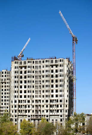 is cloudless: Big hoisting tower cranes and top section of modern construction buildings over cloudless sky