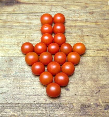 lies down: Down direction arrow built from many ripe red tomatoes lies on old vintage wooden surface Stock Photo