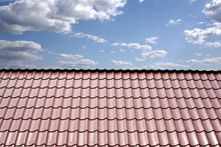 gable home renovation: Gable roof of a house covered with metal tile closeup against blue sky with white clouds Stock Photo