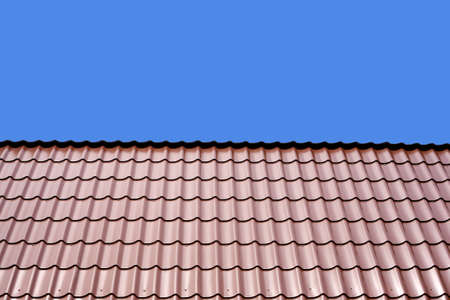 gable home renovation: Gable roof of a house covered with metal tile isolated on blue background closeup