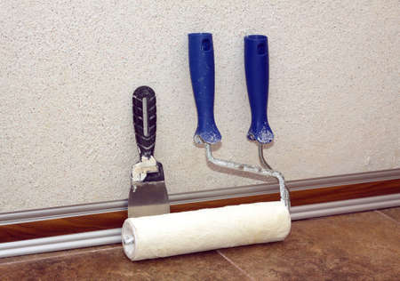 baseboard: Paint rollers with plastic blue grip and trowel stands after work in a room at baseboard on the floor near repaired wall, covered with decorative plaster closeup view Stock Photo