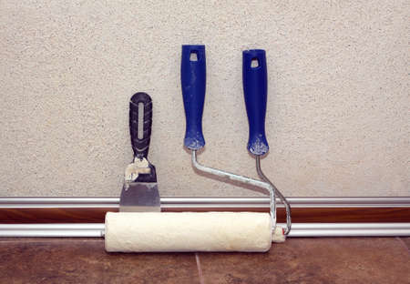 baseboard: Paint rollers with plastic blue grip and trowel stands after work in a room at baseboard on the floor near repaired wall, covered with decorative plaster front view closeup