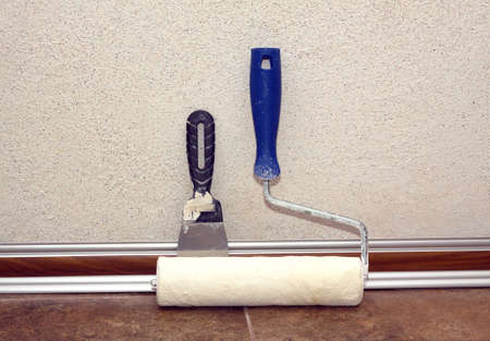 Paint roller with plastic blue grip and trowel stands after work in a room at baseboard on the floor near repaired wall, covered with decorative plaster front view closeup