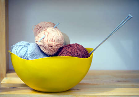 knitting needles: Color skeins of wool yarn, knitting needles and crochet hook in a big yellow bowl on wooden shelf. Photo closeup