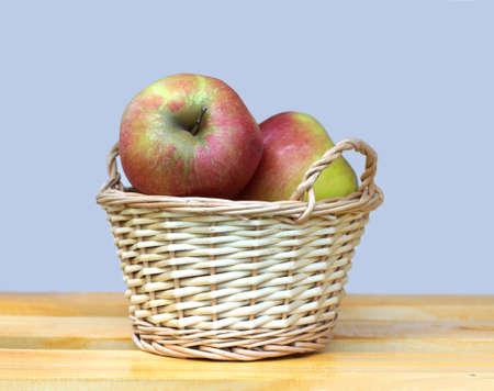 Reife rote und gelbe Äpfel BIg im hellbraunen Weidenkorb auf Holztisch gegen graue Hintergrundnahaufnahme