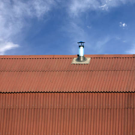 gable home renovation: Gable roof of a house covered with metal tile with short smokestack closeup against blue sky with white clouds Stock Photo