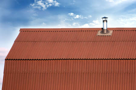 house gable: Gable roof of a house covered with metal tile with short smokestack closeup against blue sky with white clouds Stock Photo